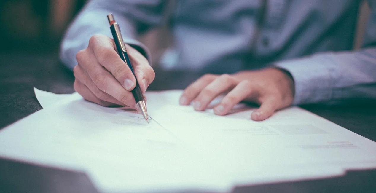 uomo che scrive su un documento