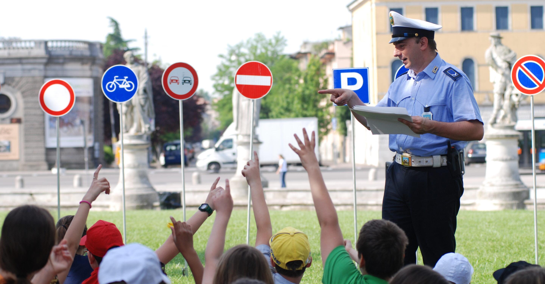 Agente di Polizia locale che insegna i cartelli ai bambini
