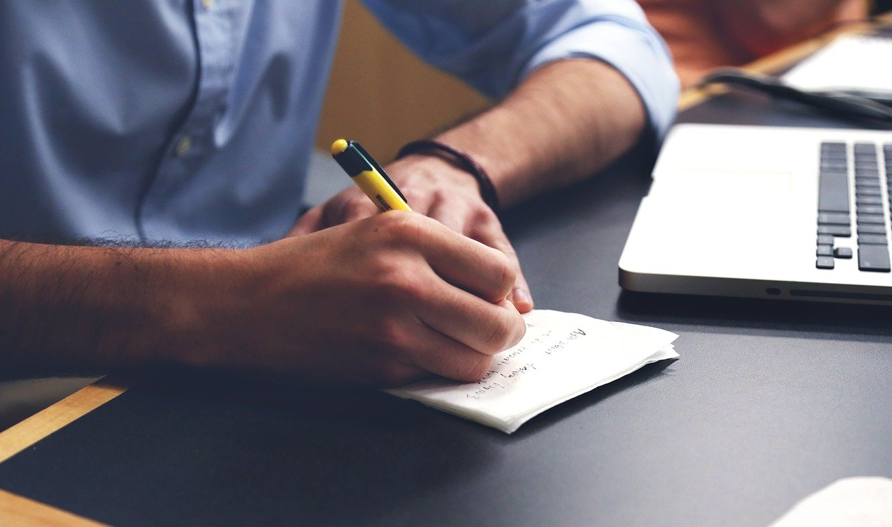 uomo che scrive su un foglio