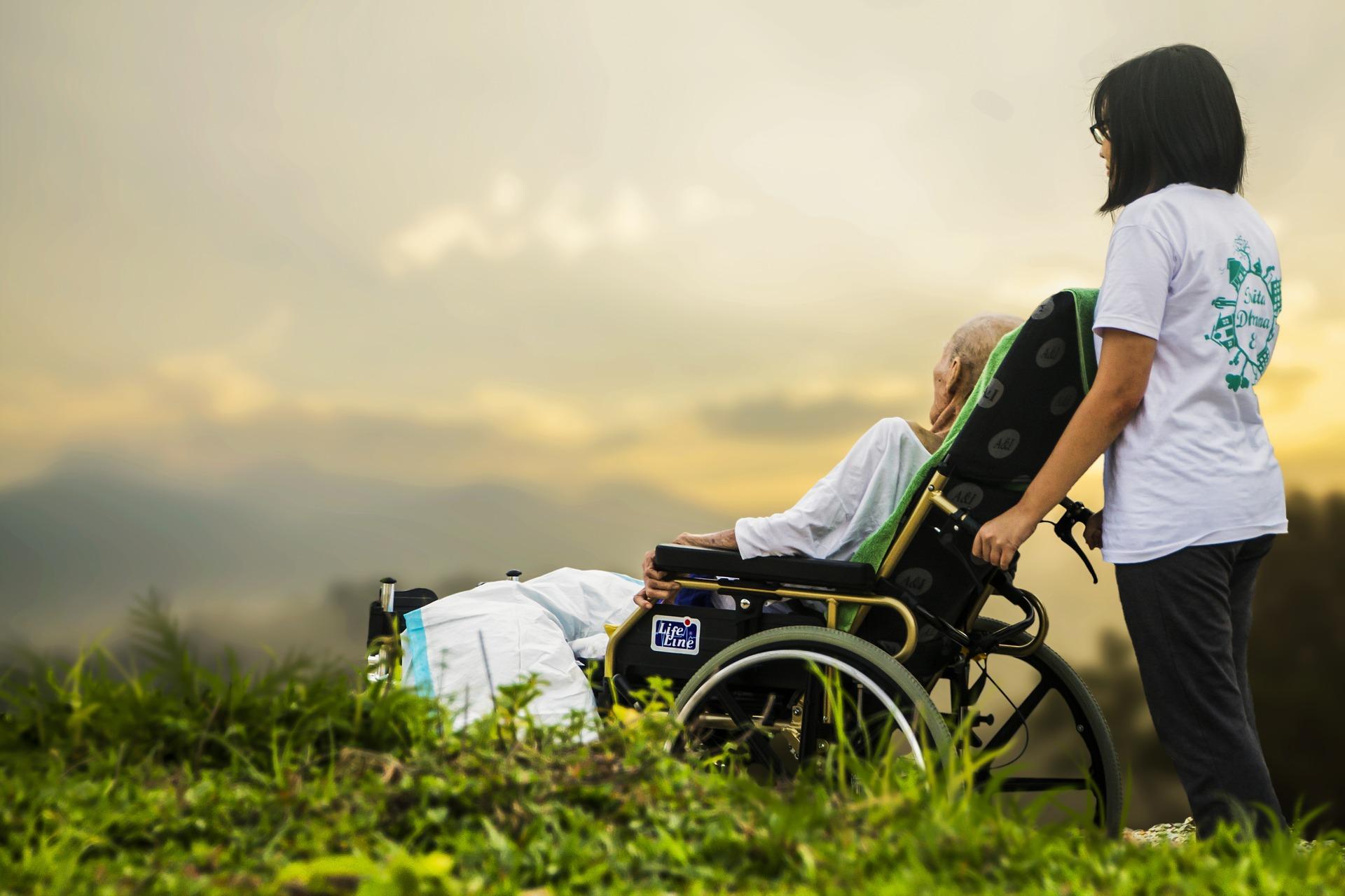 Anziano su sedia a rotello con aiuto